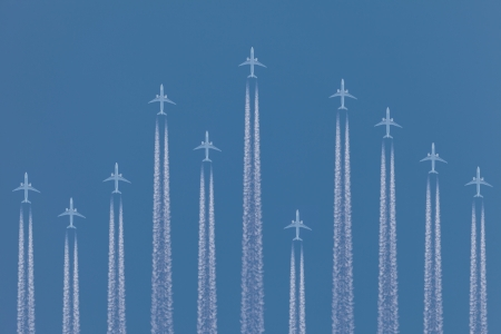 Row of airplanes flying by against a blue sky photo