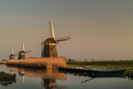 Three Dutch historic windmills in a row during sunset with a small river and boats in front photo