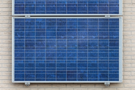 Blue solar panels attached to a vertical wall of a house Stock Photo - 15047062