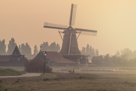 Dutch windmill on a foggy afternoon at the Zaanse Schans in Holland photo