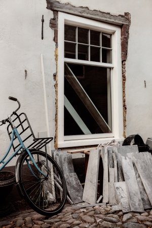 house under construction: Retro styled image of restoring an old Dutch house with bicycle in front Stock Photo
