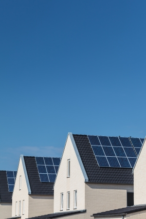 Row of new white houses with solar panels on the roofs in a row photo