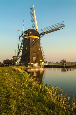 Dutch historic windmill during sunset with a small river in front photo