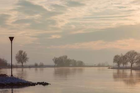 The Dutch river IJssel during a colorful sunset in winter with snow on the rvierbank photo
