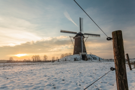 Traditional Dutch windmill in winter during sunset with wooden fence in front photo