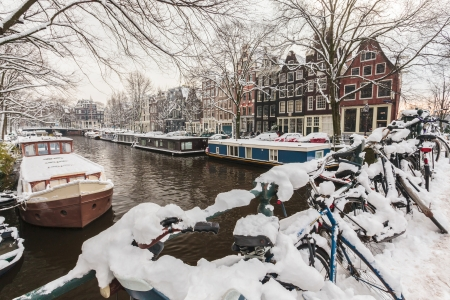 Bicycles covered with snow on a bridge during winter in Amsterdam photo