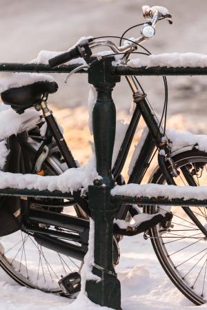 january sunrise: Bicicleta dama negro cubierto de nieve en un puente del canal en Amsterdam