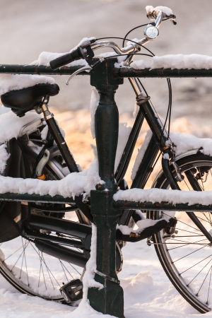 december sunrise: Black lady bicycle covered with snow on a canal bridge in Amsterdam