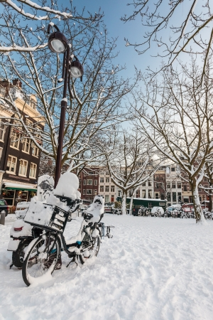 Town square with bicycles in front covered with snow in Amsterdam photo