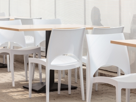 Empty canteen with white chairs and reflection of people in the background