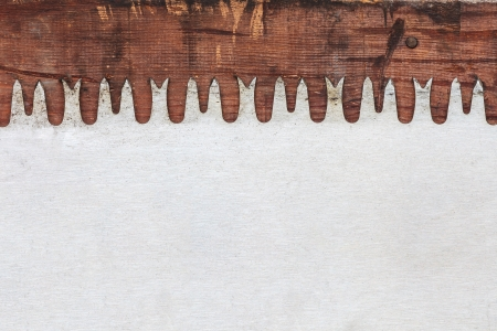 handsaw: Detail of a vintage saw blade on weathered wood Stock Photo