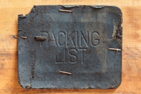 Vintage leather packing list label on a wooden background photo