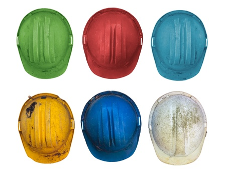 Old and worn colorful construction helmets isolated on white photo