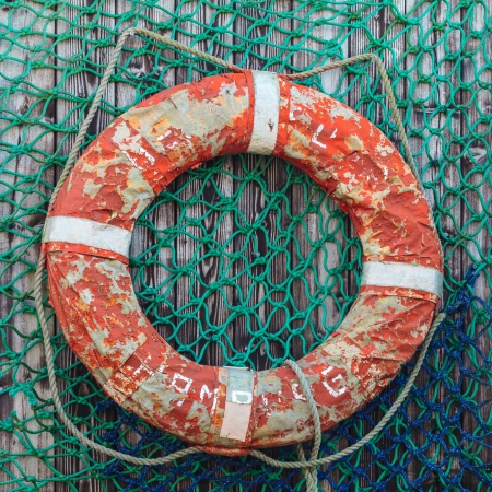 Old weathered lifebuoy on wooden wall with fishing net