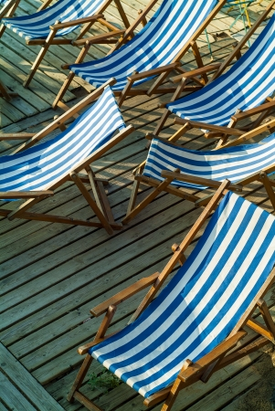 Row of empty blue and white striped beach chairs on a wooden patio  photo