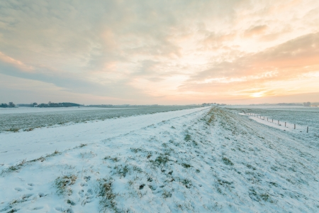 Winter landscape with a dutch dyke covered with snow photo