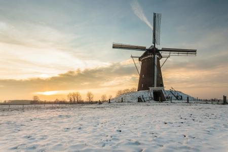 january sunrise: Molino de viento holand�s en invierno durante la puesta del sol
