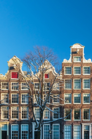 Three Amsterdam canal houses in winter with a clear blue sky