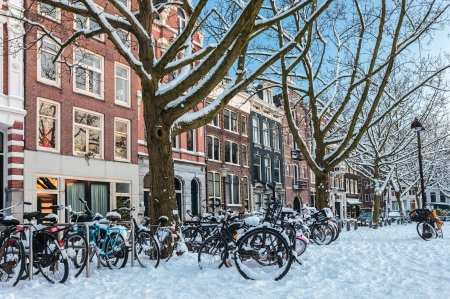 Amsterdam town square in winter with snow covered bicycles
