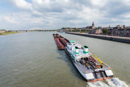 freighter: Cargo riverboat passing the Dutch city Nijmegen on the river Waal Stock Photo