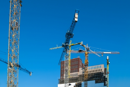 Construction of new offices with cranes against a blue sky photo