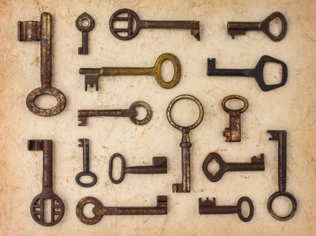 Variety of antique vintage keys on an old paper background photo