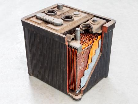 Batterie de voiture ancienne avec un corps partiellement ouverte sur un fond gris clair