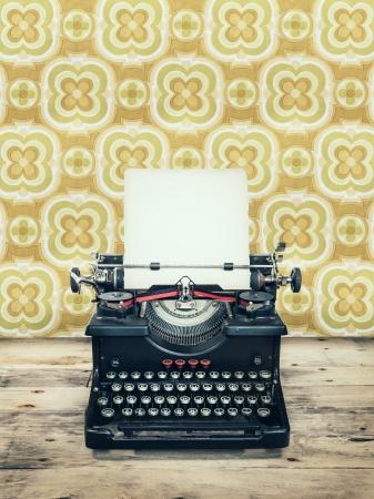 oude krant: Retro gestileerde afbeelding van een oude schrijfmachine op een houten vloer met vintage behang achter het Stockfoto