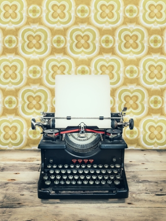 Retro styled image of an old typewriter on a wooden floor with vintage wallpaper behind it photo