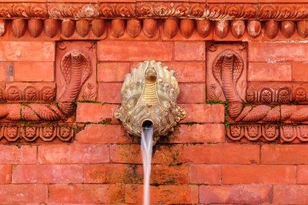 garden fountain: Old Nepalese water fountain on a red ancient wall Stock Photo