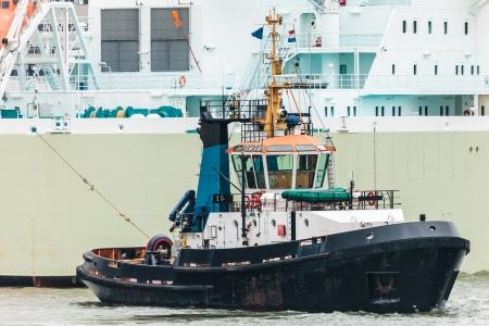 tugboat: Tugboat pulling a large sea ship in the Dutch Rotterdam harbor Stock Photo