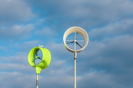Two small green and white wind turbines against a blue cloudy sky Stock Photo - 18765345