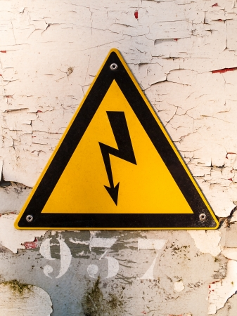 Electric hazardous area warning sign on a wall with cracked paint photo