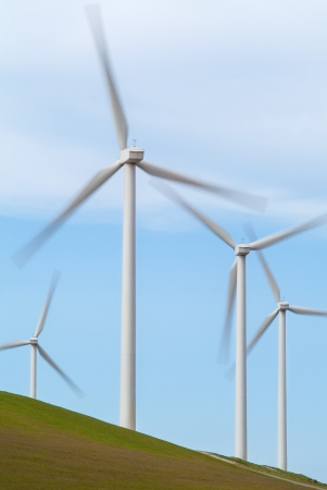 Wind turbines on a grass covered hill against a light blue sky photo
