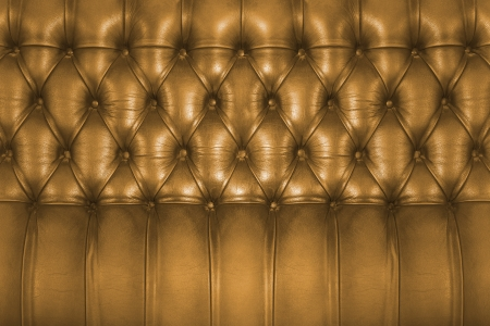 Backboard of a vintage golden brown chesterfield sofa photo