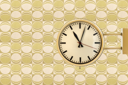Seventies vintage office clock against a retro wallpaper background with green circles photo