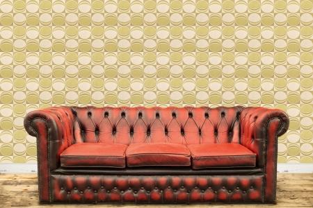 Retro Stil Bild von einem alten Sofa gegen einen Vintage Tapete Wand mit einem grünen Kreis Druck