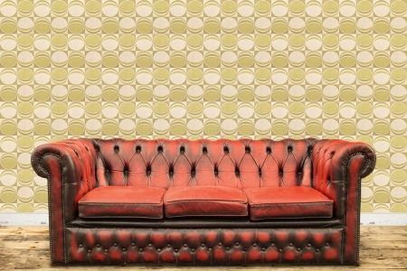 Retro styled image of an old sofa against a vintage wallpaper wall with a green circle print