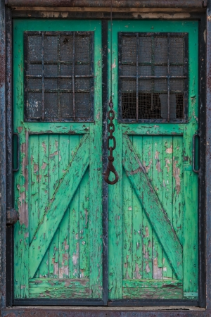 Old double green wooden warehouse door with a crane hook in front photo