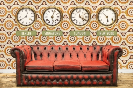 Retro chesterfield sofa with world time clocks on a wall with vintage wallpaper photo