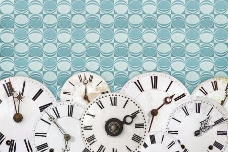 Set of vintage white clock faces against a blue retro wallpaper background photo