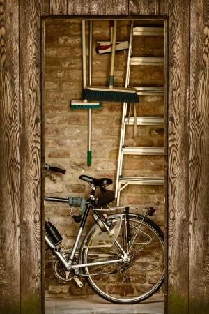 Retro style image d'un hangar avec une bicyclette et outils de jardin à l'intérieur