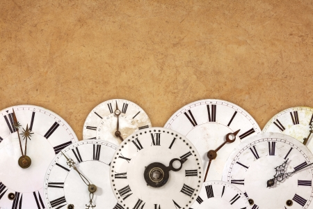 time zone: Different vintage white clock faces against an old brown textured background