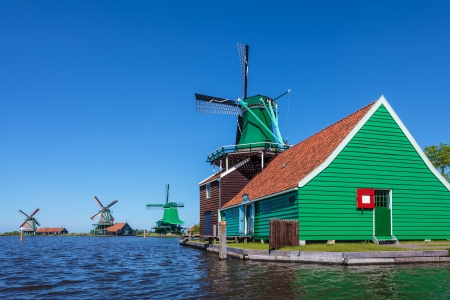 Ancient Dutch wooden windmills at the Zaanse Schans against a blue summer sky photo