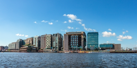 residential district: Panoramic image of modern buildings in the center of the Dutch city Amsterdam against a blue sky with water in front