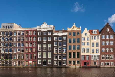 row of houses: Row of ancient canal houses in the Dutch capital city Amsterdam against a blue sky