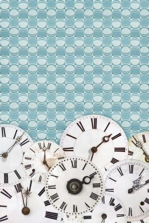 Different white vintage clock faces on a retro blue wallpaper background photo