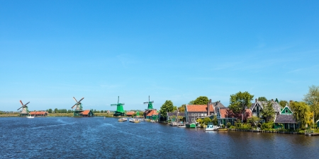 Panoramic view of the Dutch Zaanse Schans with traditional wooden windmills and houses against a clear blue sky photo