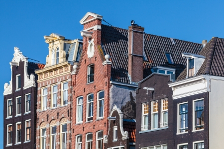 Row of ancient canal houses in the Dutch capital city Amsterdam against a blue sky photo