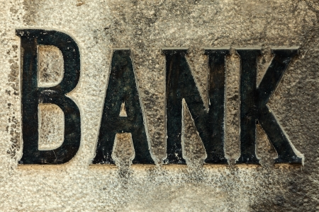 recession: Retro styled image of an old bank sign carved in a stone wall Stock Photo